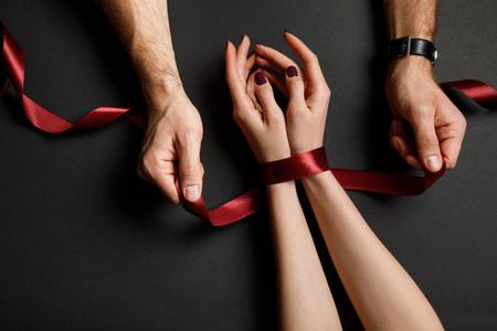 Vista recortada del hombre atando la cinta de raso rojo en manos femeninas Foto de archivo