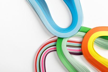 top view of wavy rainbow paper lines on grey background with copy space