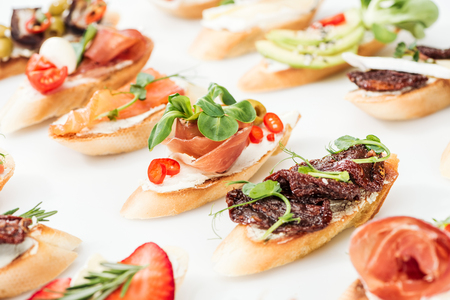 selective focus of italian bruschetta with dried tomatoes, prosciutto, salmon and herbs on white Stock Photo