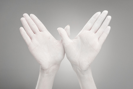 cropped view of female hands painted in white showing bird-shape sign on grey Banco de Imagens