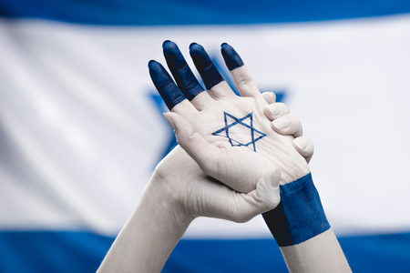 cropped view of female hands with star of david  near flag Stock Photo