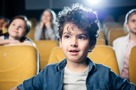 selective focus of cute mixed race boy watching movie in cinema together with friends Foto de archivo