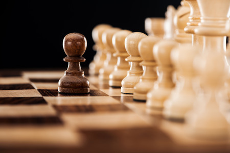 selective focus of wooden chessboard with beige chess figures and brown pawn in front isolated on black