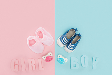 top view of pacifiers, booties, sneakers and boy, girl lettering on pink and blue background