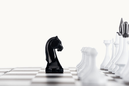 selective focus of chessboard with white chess figures and black knight isolated on white