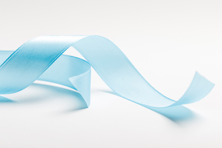 close up of curved blue ribbon on grey background Stock Photo