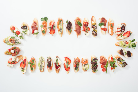 top view of arranged italian bruschetta with prosciutto, salmon, fruits, vegetables and herbs on white Stock Photo