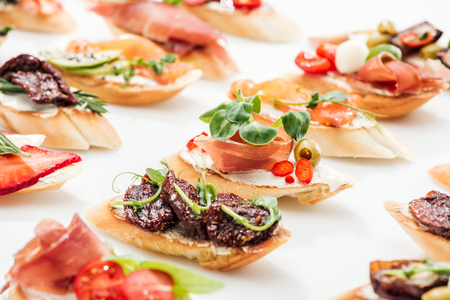 selective focus of italian bruschetta with dried tomatoes, prosciutto and herbs on white