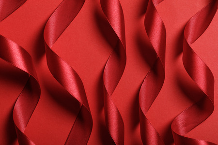 close up of wavy silk red ribbons on red background