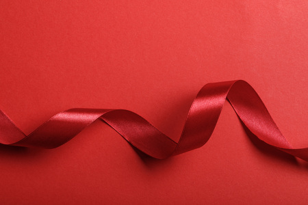 top view of wavy silk red ribbon on red background with copy space