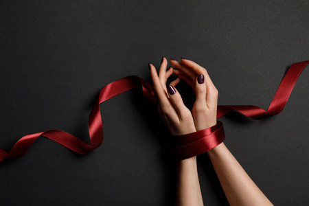 cropped view of woman tied with silk red ribbon on black background