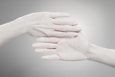 cropped view of female hands painted in white on grey Banco de Imagens