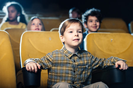 concentrated boy watching movie in cinema together with multicultural friends