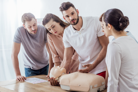 man holding cpr dummy and looking at camera during first aid training class with group of people