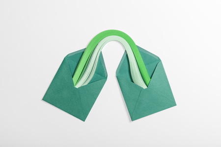 top view of green paper envelopes with multicolored rainbow on grey background