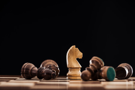 selective focus of chessboard with scattered wooden figures and knight isolated on black Stock Photo