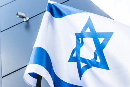 low angle view of national flag of israel with star of david near building
