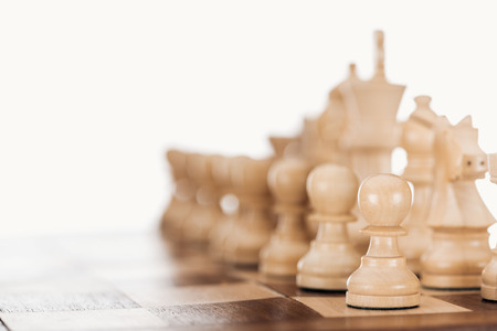 selective focus of beige and brown wooden chessboard with chess figures isolated on white