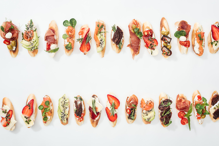 top view of delicious traditional italian bruschetta with prosciutto, salmon, fruits, vegetables and herbs on white Stock Photo