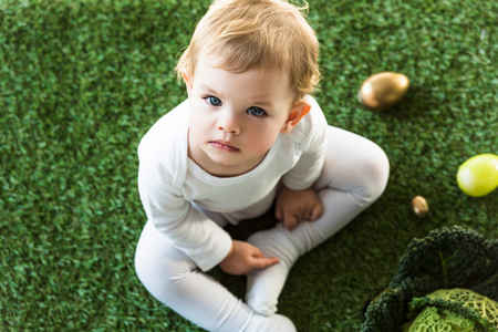 dreamy child sitting on green grass near Ester eggs and savoy cabbage, and looking at camera Stock Photo