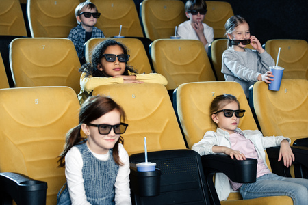 smiling multicultural friends in 3d glasses watching movie in cinema