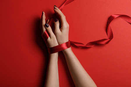partial view of woman tied with satin ribbon on red background