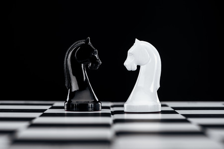 selective focus of chessboard with white and black knights isolated on black