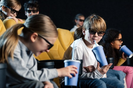 selective focus of smiling multicultural friends in 3d glasses holding paper cups Stockfoto