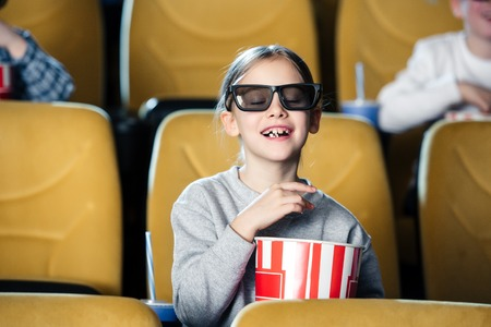 cute child in 3d glasses with closed eyes eating popcorn from paper cup