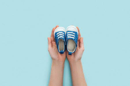 partial view of adult man holding sneakers on blue background with copy space Stok Fotoğraf