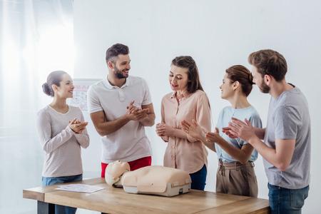 Gruppe lächelnder Menschen mit CPR-Dummy, die während des Erste-Hilfe-Kurses applaudieren