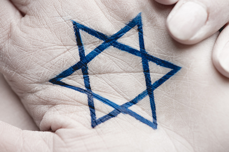 close up of female hands with jewish star of david on grey Stock Photo