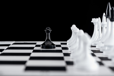 selective focus of chessboard with white chess pieces and black pawn in front isolated on black