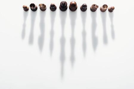 bovenaanzicht van bruine schaakfiguren met lange schaduwen op witte achtergrond Stockfoto