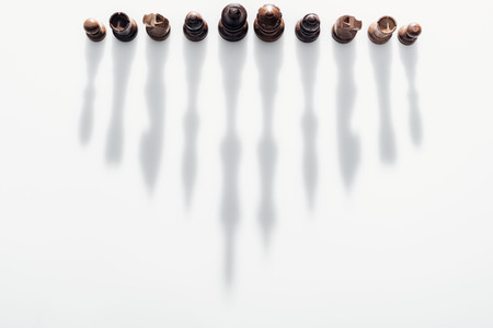 top view of brown chess figures with long shadows on white background