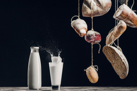 homemade bread hanging on ropes near splashing milk isolated on black with copy space