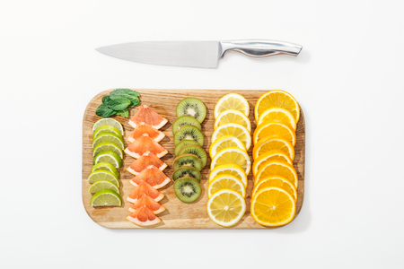 Top view of wooden cutting board, knife and cut fruits on white surface