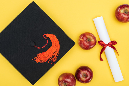 Top view of academic cap, diploma and apples on yellow surface