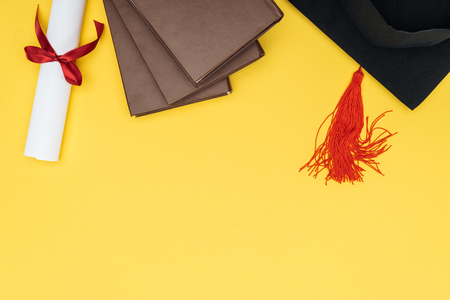 Top view of books, academic cap and diploma on yellow surface 写真素材