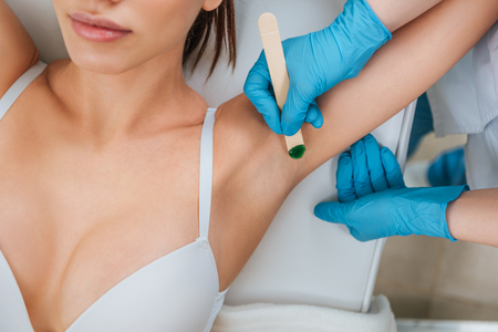 Cropped view of cosmetologist using putty knife for armpit wax depilation