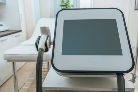Laser machine with blank screen near beauty couch in clinic Stock Photo