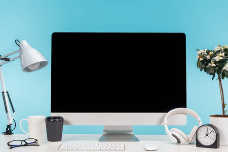 workplace with computer, lamp, cup, coffee to go, clock and flowerpot on white table on blue background Stock Photo