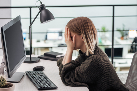 upset girl sitting at workplace with hands on face in modern office
