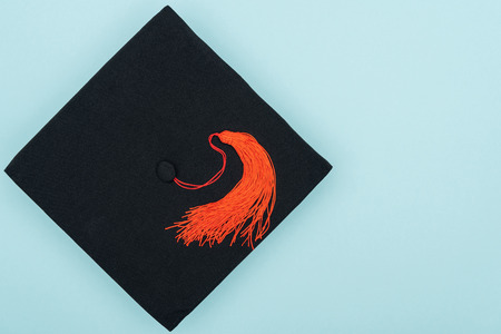 Top view of academic cap with red tassel isolated on blue