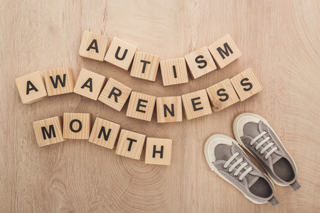 top view of autism awareness month words made of wooden blocks near grey children sneakers