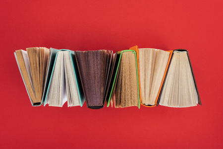 Top view of hardcover books on red surface