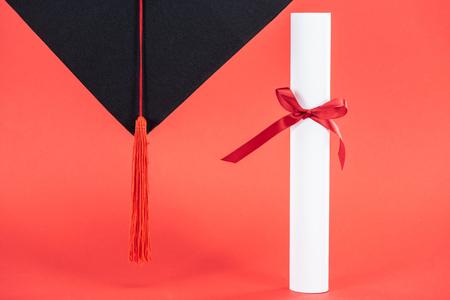 Academic cap with tassel and diploma with ribbon on red surface Фото со стока - 120484707
