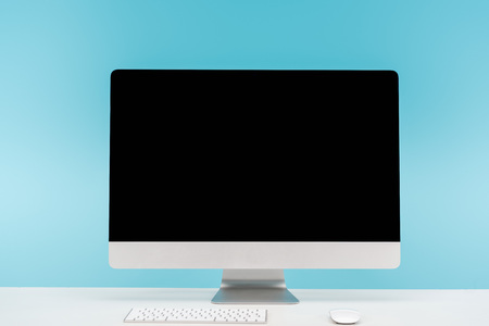 workplace with computer monitor, keyboard and computer mouse on white table on blue background