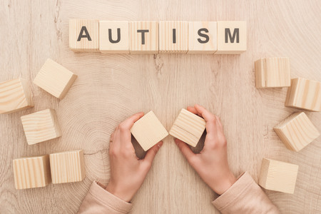 partial view of woman holding empty wooden cubes near autism lettering