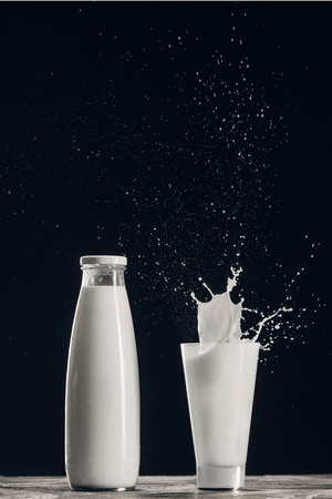 splashing milk in glass near bottle isolated on black